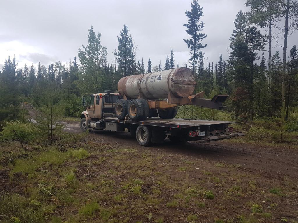 Heavy cylindrical pipe being towed away