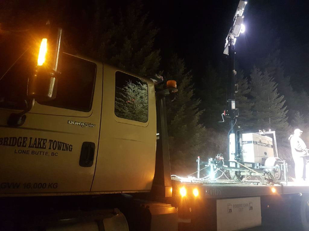 View of a flat bed tow truck at night